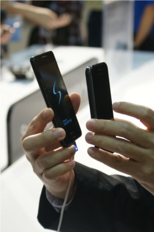 The Galaxy S II and Galaxy S held up side by side, distinctly showing the former to be thinner than its predecessor.