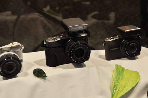 Shown here are NX100 cameras with the flash (center) and GPS attachments (right).