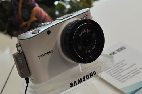 The NX100 is smaller and lighter than the NX10. It comes in white, black, brown and silver.