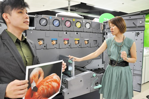 Fuji Xerox staff showing the media print samples as well as explaining the mechanics behind the Fuji Xerox Color 1000. At the extreme top right of the machine, the clear dry ink station can be seen.