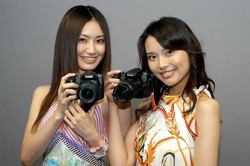 Models proudly showcasing the Sony Alpha A100. Look carefully and you could probably make out the size of the camera from their handling.