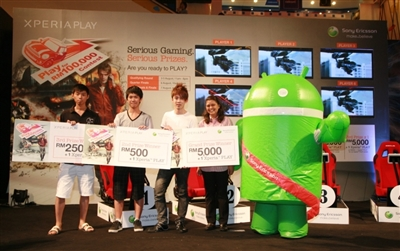 From L-R: 3rd place winner Goh Yong Seng, 2nd place winner Phong Khai Loong and champion Lim Meng Kit with their mock checks on stage. Also with them is Sony Ericsson Malaysia Logistics Manager Aida Abu Bakar and the Android mascot.