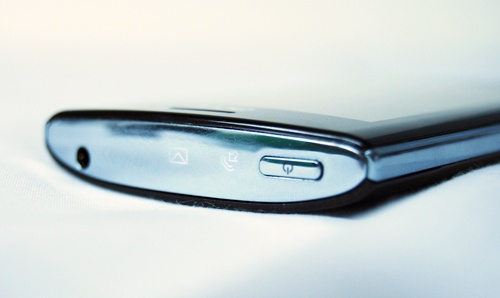 From left to right – battery status, an envelope/messaging icon, and an arrow symbol. The messaging icon pulses when there are unread messages, while the arrow symbol lights up to inform you of missed or incoming calls. Both the 3.5mm headphones jack and power button flank the sides.