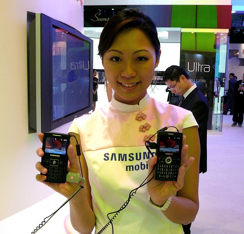 Held in her hands are the i600 and the older i320N models. The two phones don't look very different in shape and size, which is amazing because Samsung has packed in so many wireless features without increasing the size of the phone. Can you guess which is which?