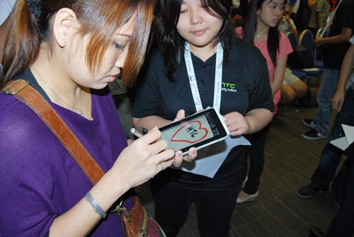 A HTC promoter showing an eager participant how to use the HTC Flyer's Scribe functions.