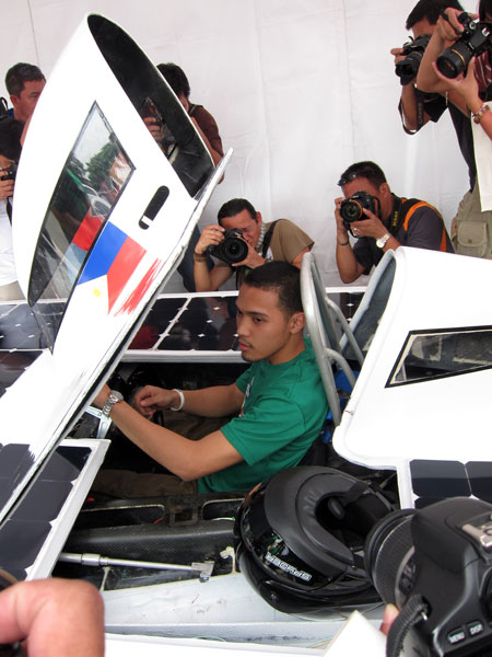 A member of Team Solar Philippines shows off what it's like to take the wheel on the Sikat II.