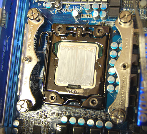 After fitting the backplate, it's time to screw in the mounting brackets for the cooler. In this case, for the Intel LGA1366 socket, there are two separate pieces. As you can see here, they don't interfere with the CPU latch, so you can change a processor without removing the bracket.