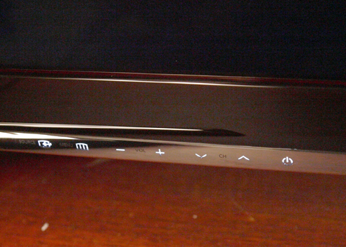 A row of touch-sensitive controls are positioned across the lower edge of the TV.  The lights come into view when contact is made. As far as tech gadgets go, subtlety is sexy.