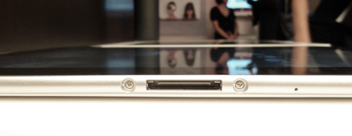 A charging port sits at the bottom of the tablet.