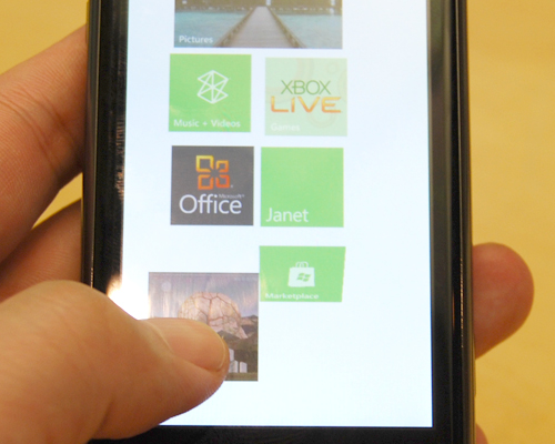Adding specific multimedia files onto the screen as a live tile is possible on Windows Phone 7.