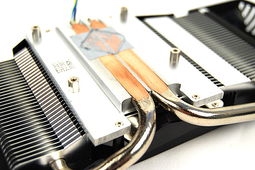 "We removed the cooler to take a closer look at the DirectCU technology. Here, we can clearly see the two copper heat pipes that will be in direct contact with the GPU core. Strangely, ASUS has opted to give the heat pipes an aluminum finishing; perhaps they feel ""copper orange"" will disrupt the color theme of the product or scientifically taking advantage of aluminum's properties to radiate heat better while allowing copper to act as the better heat conductor."