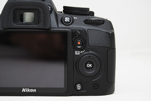 In comparison to the integrated Live View flip and video Record switch found on the D3100 (pictured) and the D7000, which we think is a better implementation.