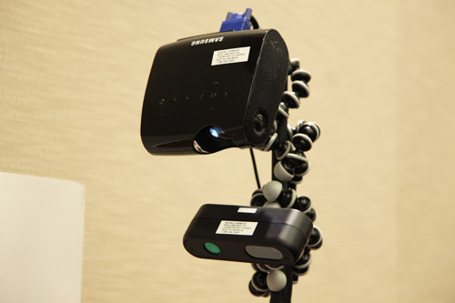 An RGB-D camera and a projector are used to enable image recognition and create the surface-based user interface.