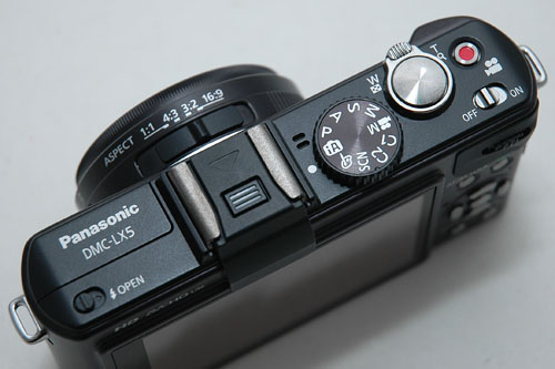 Note the new bright red movie record button next to the shutter release, as well as the 1:1 aspect ratio switch on the lens.