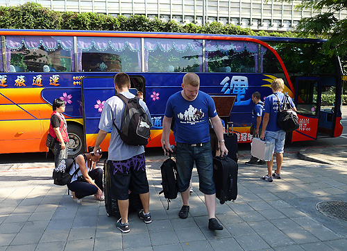 Contestants unloading their gear from the tour bus.