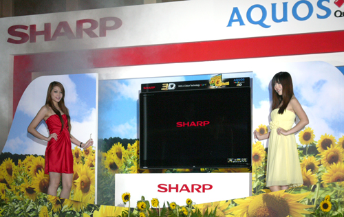 Two babes flank the 3D AQUOS Quattron during its unveiling ceremony. In a nutshell, Sharp's Quattron technology was designed to render hues such as yellow, gold and emerald green in more vivid shades.
