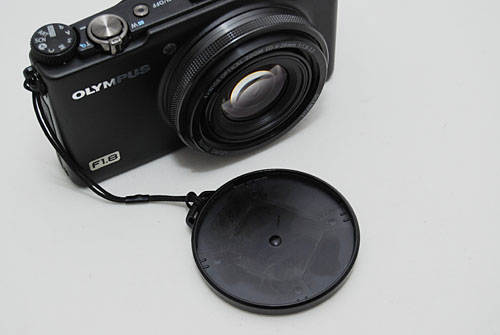 The lens cover is simply a plastic top, which means it can be easily pushed out of the way by the lens extending and also easily loosened in a bag.