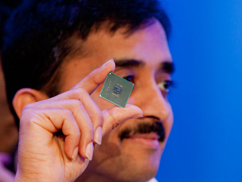 Intel researcher holding up the prototype x86 low power chip.