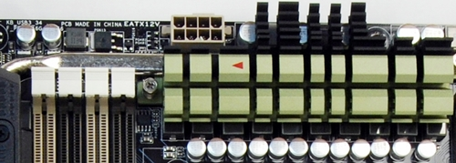 The silver heatpipe extends from the olive green heatsink into the TUF Thermal Armor I/O port plastic sheath. Notice the tiny red arrow indicating the direction of the heat flow.