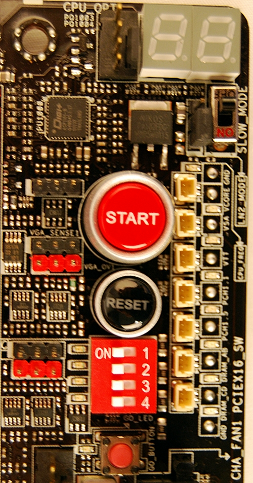 In the top right hand corner below the Debug LEDs, the Slow Mode switch is employed during LN2 benching. Flipping it will 'slow' the CPU to prevent the system from crashing when attempting to boot into the OS at cold temperatures. The red 'GO' button enables ASUS' MemOK! feature to fix memory incompatiability issues before booting into the OS.