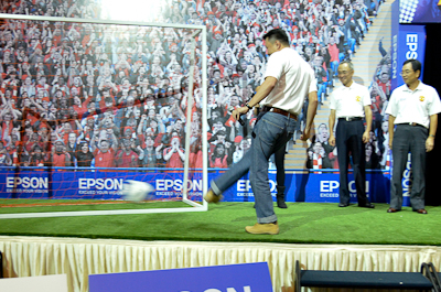 Danny Lee, General Manager of Sales and Marketing Division, Epson Malaysia kicking a ball to officiate the launch of the projectors here in Malaysia. Looking on are (L-R) Yasuhiro Kasai, Country Manager of Epson Malaysia, and Eiji Ide, Managing Director of Epson Singapore Pte Ltd.