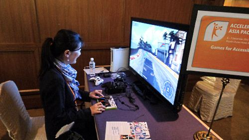 A participant tries out a gaming demonstration featuring accessible controls for those with special needs