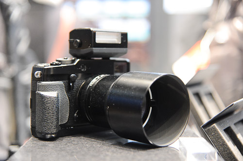 A tricked-out X-Pro 1 with flash attachment, additional hand-grip and lens hood.