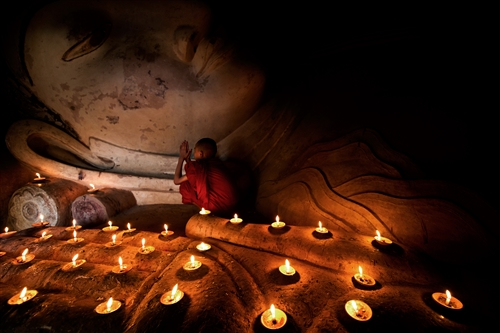 Teng Hin Khoo: The sleeping Buddha statue was inside a dark cavern below one the many temple ruins in Bagan, Myanmar. The scene was mainly lighted by the candles and a small stream of natural light from the small doorway.