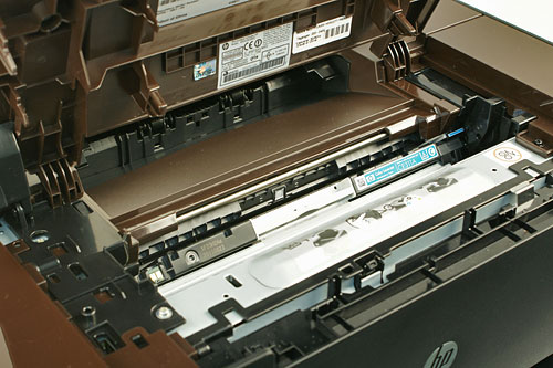 Below the capture stage is the toner cartridge compartment. If the cartridge at the opening isn't the one that you want to replace, you can go to the home screen of the control panel, navigate to the Supplies menu, and select Cartridge Rotate to turn the cartridge carousel.