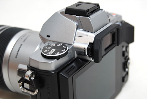 The hump on top of the E-M5 houses the electronic viewfinder, hot shoe adapter and accessory port. The camera does not have a built-in flash.