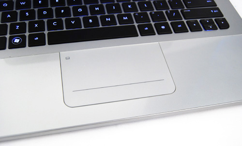 The track pad is flush with the glass wrist rest, making it slightly elevated from the keyboard.