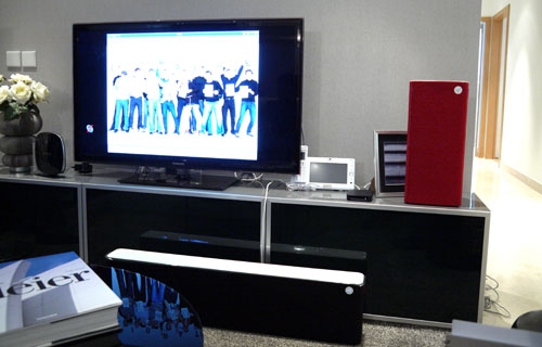 Here's Libratone's general setup in a mock living room. The Libratone Live (far right, in red) is configured as a standalone device here, while the Libratone Lounge (below, in black) is connected to the Apple TV media receiver via an optical cable.