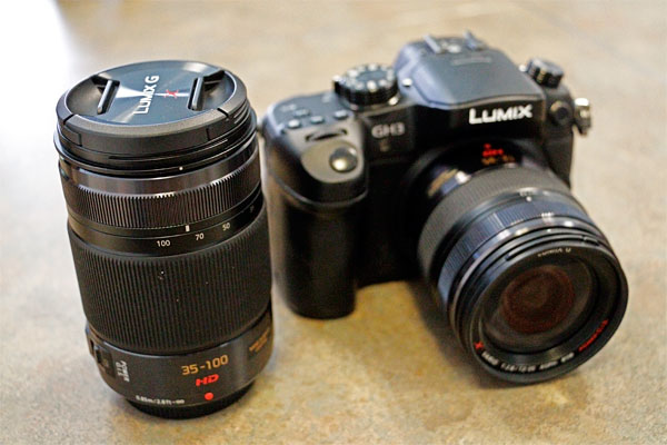 The Panasonic 35-100mm f/2.8 lens next to a GH3 with a 12-35mm f/2.8 lens attached.