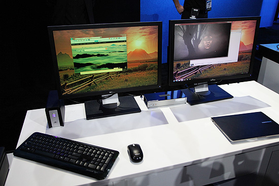 The WiGig demo with two wireless displays and a wireless storage drive (to the left) connected to the Ultrabook (to the lower right) without any cables. The WiGig prototype router is the black box with the white front panel located in between the two monitors.