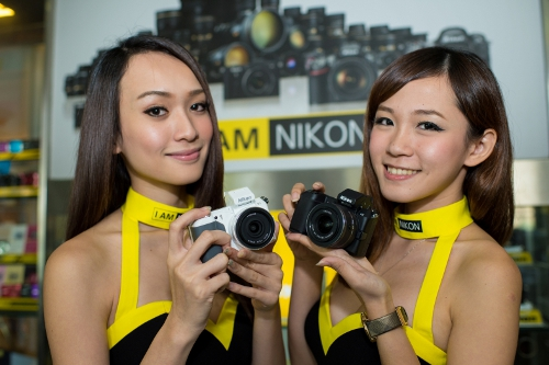 Models showing off the Nikon 1 V2 cameras which feature a i-TTL compatible built-in flash