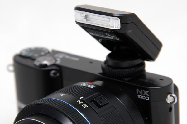 The flash attachment can be pushed down for stowing, but to shoot with flash you have to raise it.