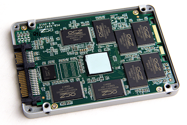 The new Indilinx Barefoot 3 controller (IDX500M00-BC) is concealed by a thermal pad. Surrounding it are eight NAND memory chips of 16GB density, OCZ-branded by actually supplied by IMFT. Finally, the smaller chip to the left of the controller is a 256MB DRAM chip from Micron.
