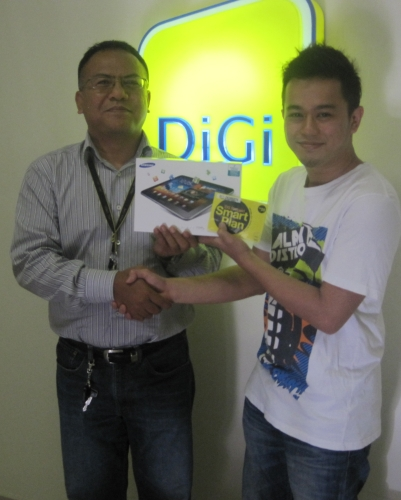 DiGi Deep Green Handset Recycling Campaign Winner from JB, Ahmad Fairuzhab bin Abdul Rahim (right) receiving his prize from Samsudin b. Sujak of DiGi