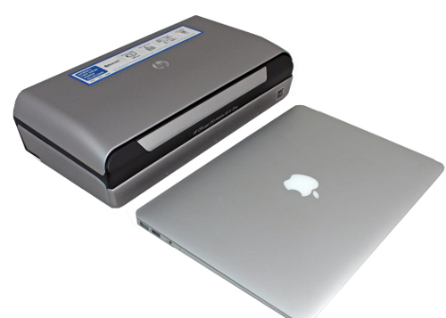 The HP Officejet 150 placed side by side with an Apple MacBook Air for relative size comparisons.