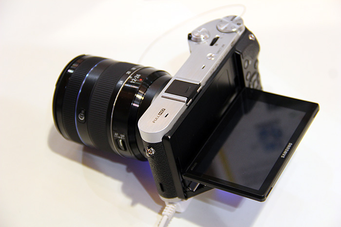 The NX300's screen tilts, but only up and down, not to the side.