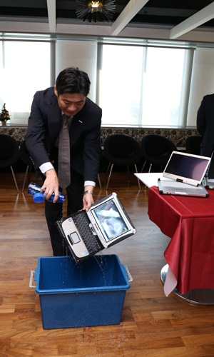 Satoshi Mizobata giving a demonstration on the waterproof capabilities of selected Toughbook models