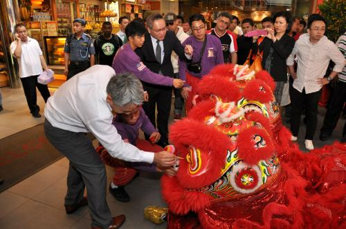 Mr. Niizuma and Mr. Lee seen here being guided by a lion dance troupe member on painting the eyes of the lion's head