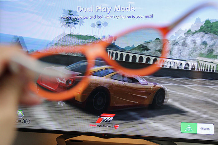 For two-player games, instead of splitting the screen, Dual Play allows the whole screen to be used by each player. This is done by transmitting two separate 2D images that can be seen through two different sets of polarized glasses. In this example, this pair of glasses can only see the red car; the other pair will only see the yellow car.