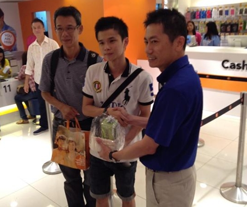 Yip (in white polo tee) queued a day earlier so that he could get the gold iPhone 5S. Joseph Lok (right), General Manager of M1 Shop Paragon congratulated him on his purchase.