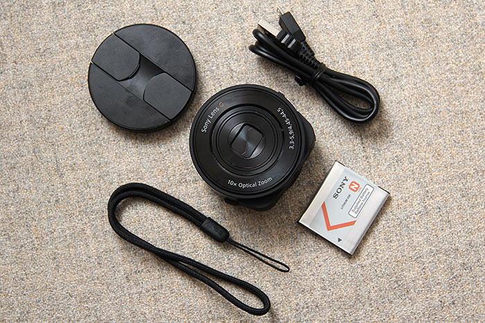 The Cyber-shot DSC-QX10 comes with a smartphone attachment which lets you mount the camera onto your phone. Other items in the box include the battery, USB cable, and wrist loop.