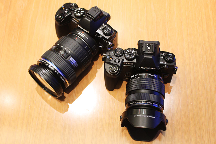 The E-M1 with a Four Thirds adapter and a Zuiko Digital lens (left), and an E-M1 with the new 12-40mm f/2.8 M.Zuiko Pro lens for Micro Four Thirds (right).