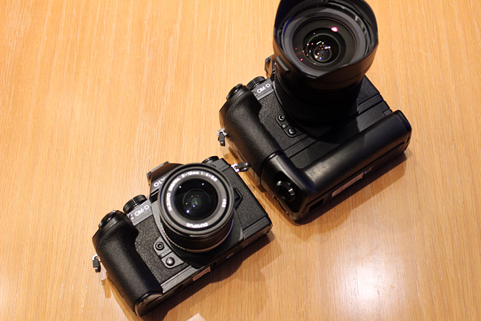 The E-M1 with a battery grip attached (right). It's a different model than the one used on the E-M5.