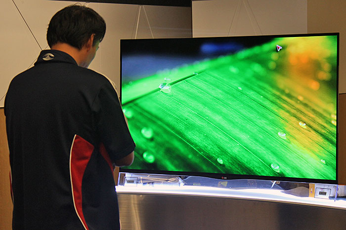 An attendee admiring the picture quality of the 55EA9800 OLED TV, which sports LG's 4-color pixel (WRGB) technology.