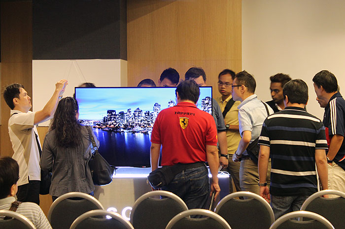 Besides a stunning picture, the 55EA9800 curved OLED TV has a carbon fiber-reinforced plastic back not common in other TVs, which explains why the attendees are crowding behind it.