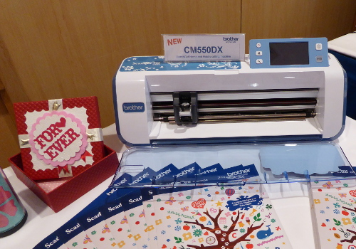 "The ScanNCut CM550DX helps to produce hand-drawn designs and even text, such as the ""Forever"" found on the card beside the ScanNCut CM550DX."
